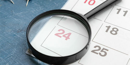stock image of a magnifying glass over a calendar